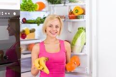 Refrigerador da laranja da banana da mulher Fotos de Stock