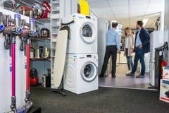 Refrigerador de compra de Assisting Couple In do vendedor imagem de stock