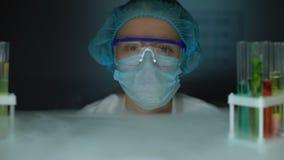 Refrigerador de la abertura del científico y el mirar a la cámara, profesional el lugar de trabajo metrajes