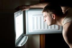 Refrigerador hambriento de la apertura del hombre. Fotografía de archivo libre de regalías