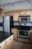 Refrigerador inoxidable de las cabinas de madera de la cocina Imagen de archivo