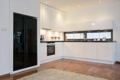 Refrigerador negro en cocina brillante Imagen de archivo