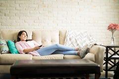Refrigerando em casa a tevê de observação imagem de stock royalty free