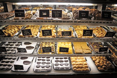 Refrigerated cookie display. Rugalatch, brownies, black and white cookies, muffins, Danish, and baklava on display in store refrigerated case Royalty Free Stock Photography