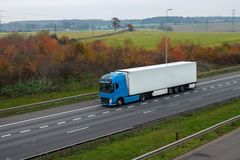 Refrigerated lorry in motion on the road. Against autumn landscape stock images