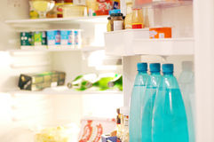 Refrigerator. An open refrigerator full of grocery items. Focus is on the bottles in the foreground, the rest of the products are blurred, no logos visible Stock Photo