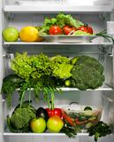 Refrigerator with Green Food. Refrigerator full of green nutritious food, vegetables and salad Stock Photo