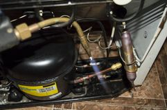 Refrigerator repair - a tool to repair a refrigerator and the repair process itself royalty free stock images
