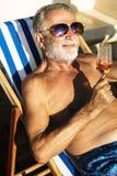 Refrigerazione senior dell'uomo e vino bevente su sdraio fotografia stock