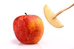 Refrigere a maçã vermelha na forquilha no fundo branco Fotos de Stock