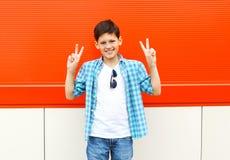 Refrigere o menino de sorriso da criança que tem o divertimento na cidade sobre o vermelho Fotografia de Stock