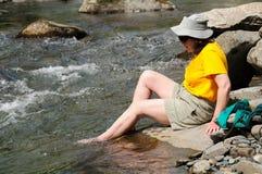 Refroidissement de vos pieds dans un flot de montagne Photos stock