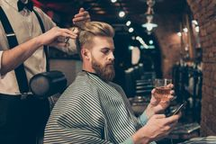 Refroidissez au salon de coiffure La vue de côté du jeune rouge beau soit images libres de droits
