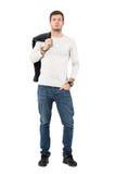 Refroidissez l'homme bel dans des jeans portant la veste en cuir au-dessus de l'épaule regardant l'appareil-photo Photographie stock