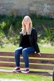 Refroidissez la fille blonde s'asseyant sur un banc en bois Photo stock