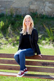 Refroidissez la fille blonde s'asseyant sur un banc en bois Images stock