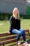 Refroidissez la fille blonde s'asseyant sur un banc en bois Image stock