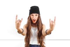 Refroidissez la jeune fille dans le chapeau noir montrant le signe des klaxons Photo stock