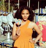 Refroidissez la vraie adolescente avec la sucrerie près des carrousels à la PA d'amusement Photos stock