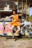 Refroidissez la vraie adolescente avec la sucrerie près des carrousels à la PA d'amusement Image libre de droits