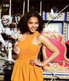 Refroidissez la vraie adolescente avec la sucrerie près des carrousels à la PA d'amusement Photographie stock libre de droits
