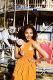Refroidissez la vraie adolescente avec la sucrerie près des carrousels à la PA d'amusement Photo libre de droits