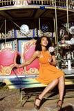 Refroidissez la vraie adolescente d'afro-américain avec la sucrerie près des carrousels au parc d'attractions, concept de personn Image libre de droits
