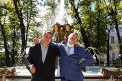 Refroidissez le marié et le sien père près de la fontaine en parc d'été Photos stock