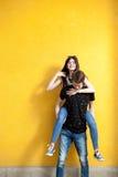 Refroidissez les jeunes couples posant dans le style de mode sur le mur jaune Photos libres de droits