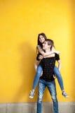Refroidissez les jeunes couples posant dans le style de mode sur le mur jaune Images stock