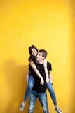 Refroidissez les jeunes couples posant dans le style de mode sur le mur jaune Photographie stock