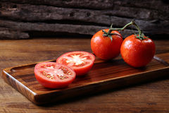 Refroidissez les tomates fraîches, entier et demi sur le plateau en bois et le Ba en bois images libres de droits