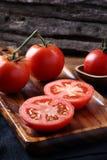 Refroidissez les tomates fraîches, entier et demi sur le plateau en bois et le Ba en bois Photos libres de droits