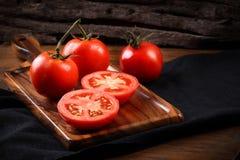 Refroidissez les tomates fraîches, entier et demi sur le plateau en bois et le Ba en bois Photo libre de droits