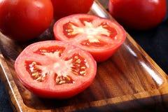 Refroidissez les tomates fraîches, entier et demi sur le plateau en bois et le Ba en bois Photos stock