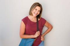 Refroidissez une femme plus âgée avec le sac à main souriant contre le mur gris Image stock