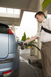 Refuel. Man on petrol station filling up his car with fuel stock photography