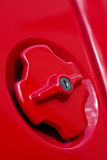 Refuel. A bright red fuel cap from a sports car Royalty Free Stock Photography