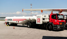 Refuel kerosene truck next to a plane at airport runway royalty free stock images