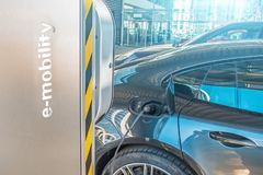 Refueling for electric cars e-mobility. Charging the machine, compartment door is open, the electric plug under voltage restores t. He battery charge Stock Photos