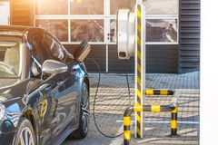 Refueling for electric cars e-mobility. Charging the machine, compartment door is open, the electric plug under voltage restores t Royalty Free Stock Photo