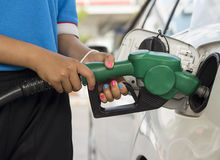 Refueling Gasoline. Woman worker refueling gasoline in gasoline station Stock Photo