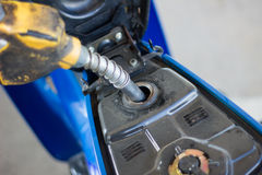 Refueling a motorcycle at a gas station in thailand Stock Image