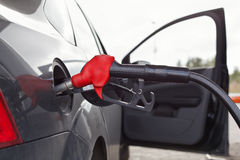 Refueling nozzle in the car Stock Image