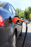 Refueling nozzle in the car stock photos