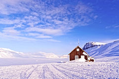 Refuge in the Arctic. Wooden shelter in the middle of a wild landscape of sea ice in the mountains on the island of Svalbard in the Norwegian Arctic Stock Photos