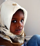 Refugee. A small muslim girl sits in the corner with a nervous expression on her face Royalty Free Stock Images