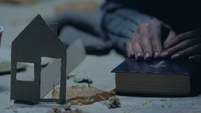 Refugee with Bible praying for home, dreaming of shelter, paper house as symbol. Stock footage stock footage