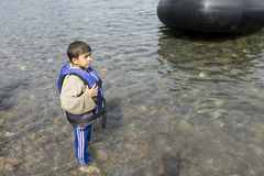 Refugee boy wearing lifejacket Lesvos Greece. Lesvos, Greece- October 12, 2015, 2015. Refugee migrants, arrived on Lesvos in inflatable dinghy boats, they stay Royalty Free Stock Photography