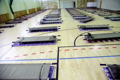 Refugee camp in school sports hall full with stretcers Stock Photo
